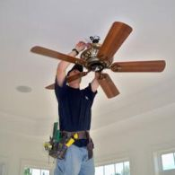 Electrician Works On A Ceiling Fan